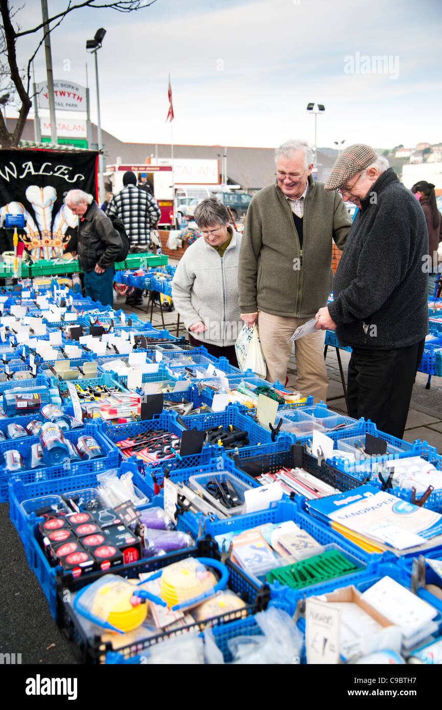 People buying cheap bargain household goods and tools on sale Aberystwyth November winter fair street market, Wales - Stock Image