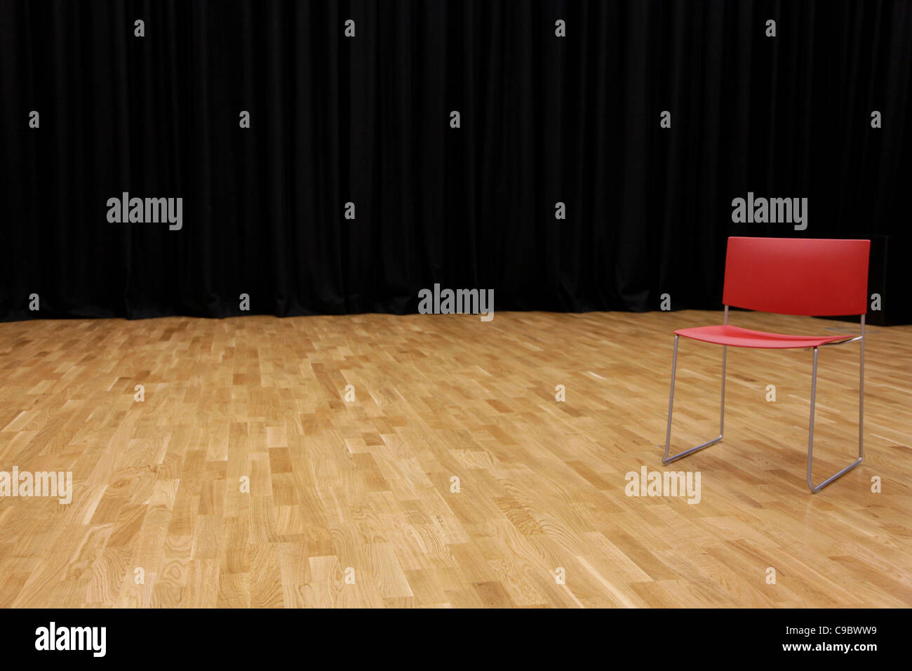 A directors chair on a stage with a black curtain in background - Stock Image