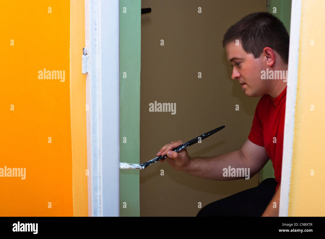 Young man painting new home. - Stock Image