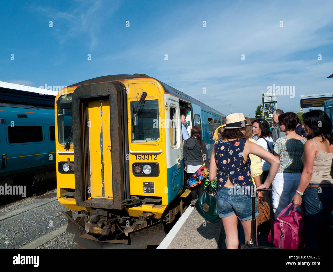 Passengers boarding an Arriva train heading for Tenby at Carmarthen Station, Carmarthenshire Walesd UK Stock Photo