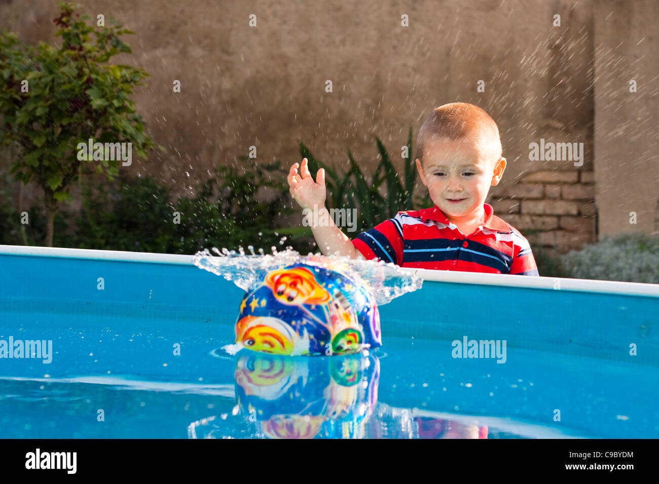 Little boy throw ball in to the swimming poll. - Stock Image