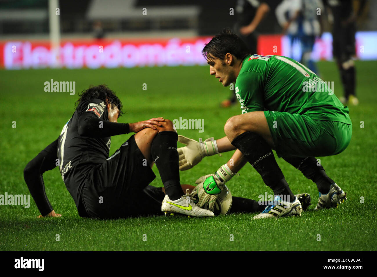 Goalkeeper helping an injured football player get up from the pitch - Stock Image