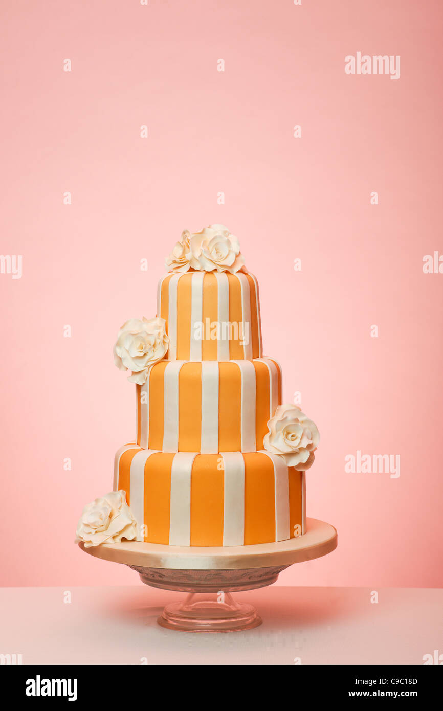 Orange striped wedding cake with peach background - Stock Image