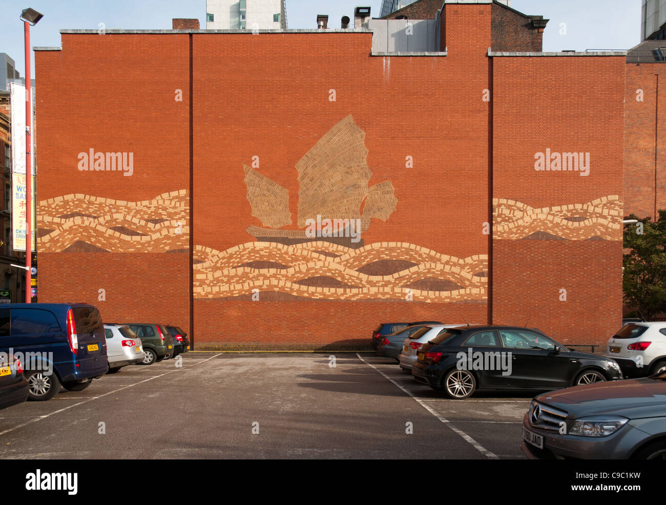 Brick mural of a Chinese junk on the wall of a car park, Chinatown, Manchester, England, UK - Stock Image