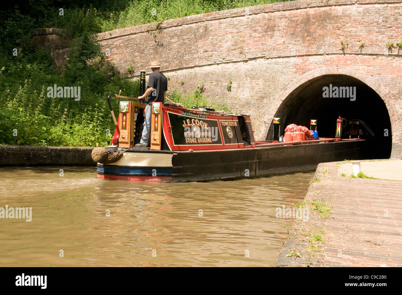 A traditional working narrowboat entering Blisworth Tunnel - Stock Image
