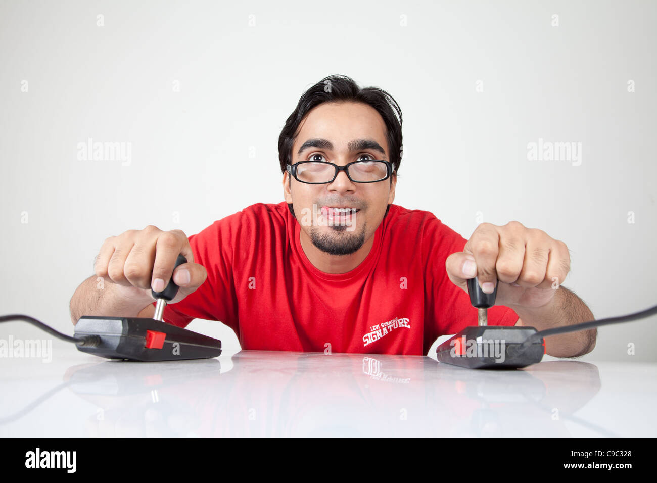 Nerd playing with two retro joystick controllers - Stock Image