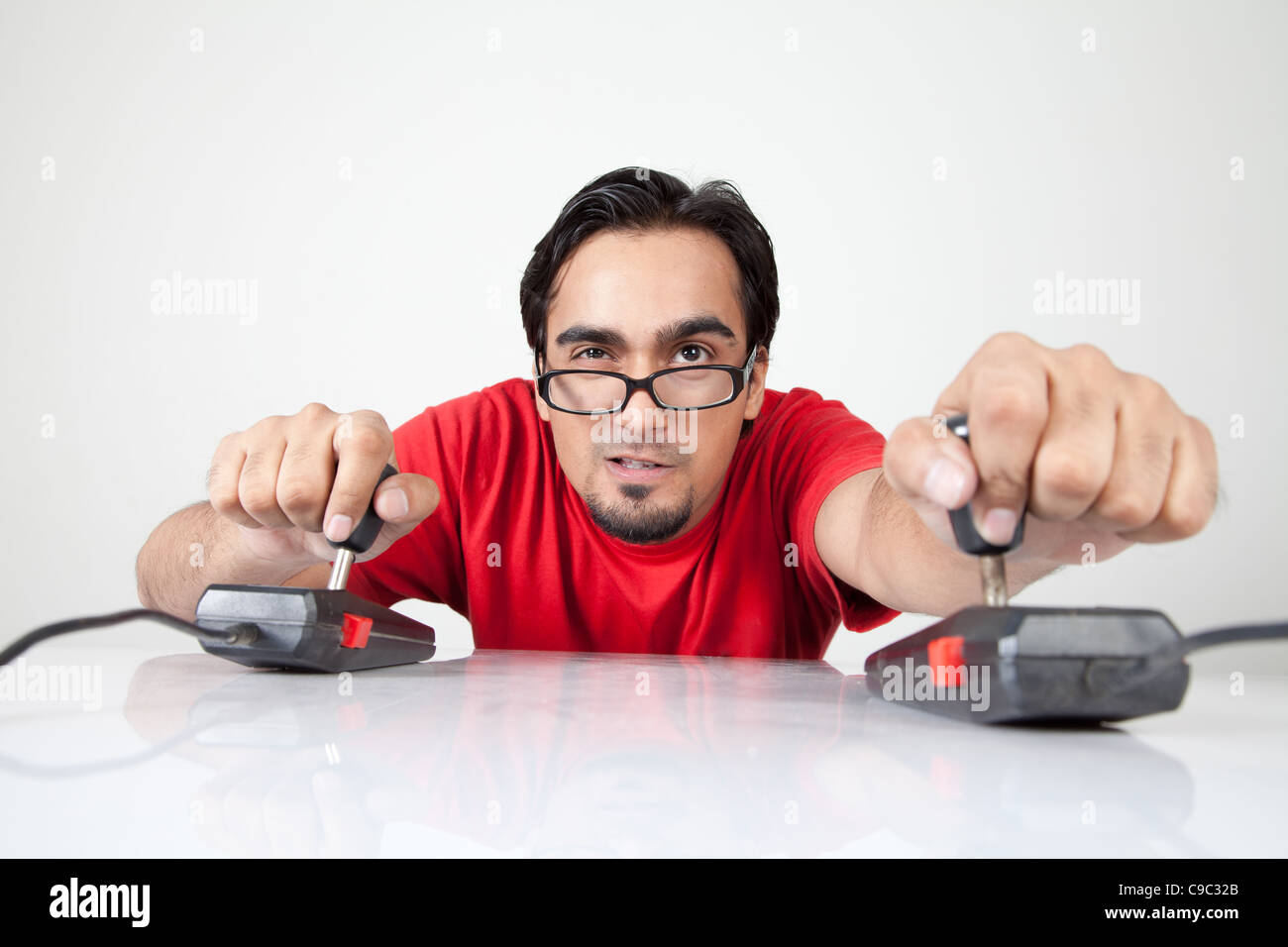 Game nerd playing with two joysticks - Stock Image