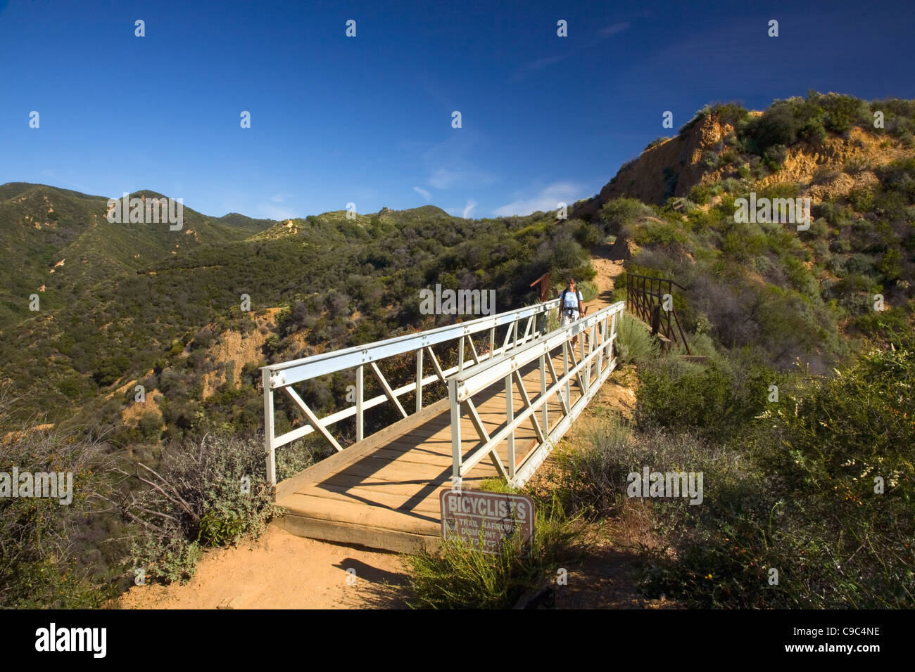 CALIFORNIA - Hiker on bridge on the Backbone Trail in the Topanga State Park section of the Santa Monica Mountains. - Stock Image