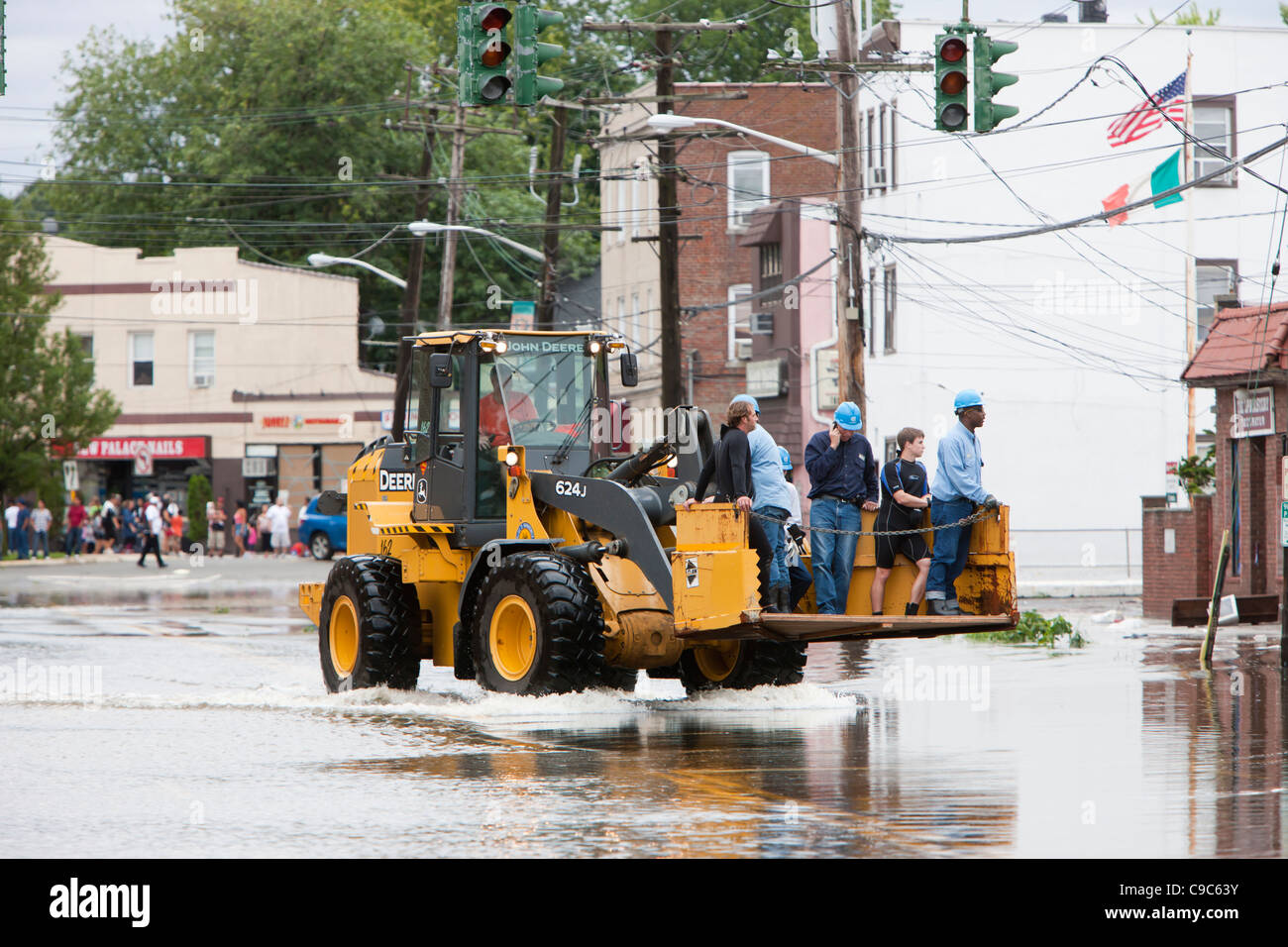 A Con Edison repair crew gets a lift in a front loader on flooded Mamaroneck Avenue in the aftermath of Hurricane - Stock Image