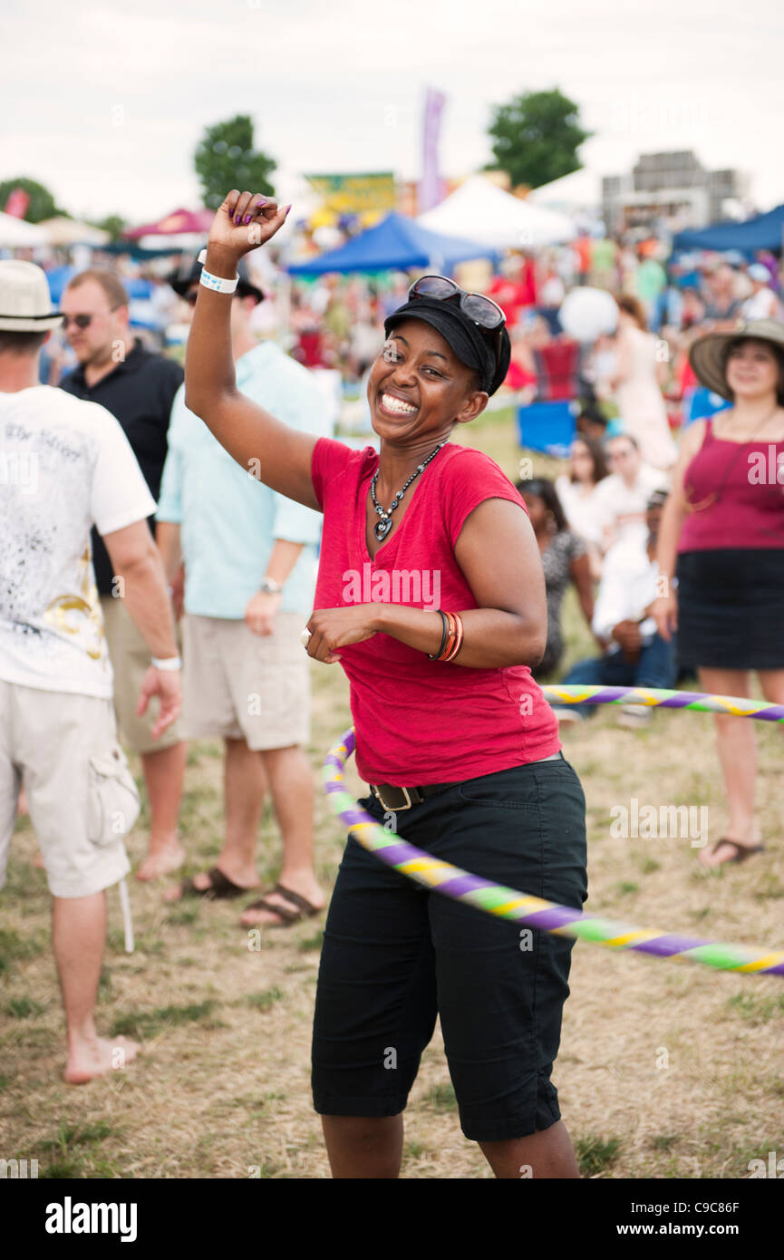 A young lady hula hoops happily at the 'Vintage Virginia Wine Festival' in Manassas Virginia. - Stock Image