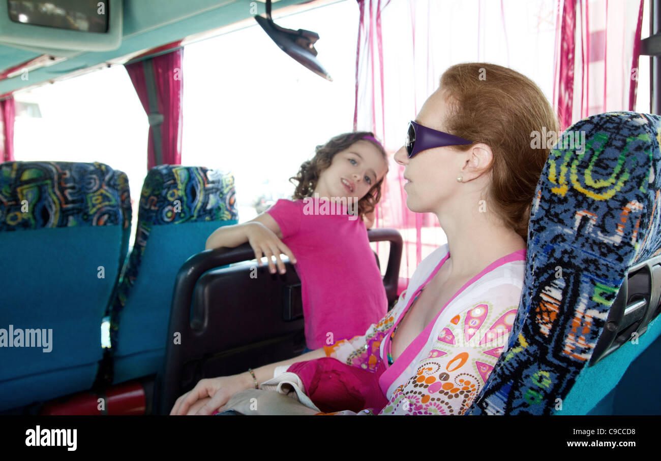 Girl and mother on tourist bus happy with sunglasses in vacations - Stock Image