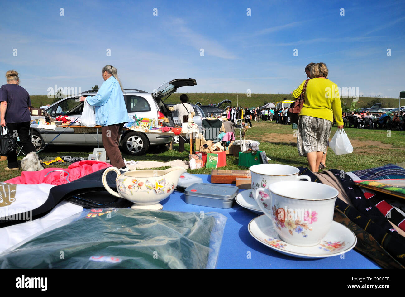 Car boot sale market with stall in foreground - Stock Image
