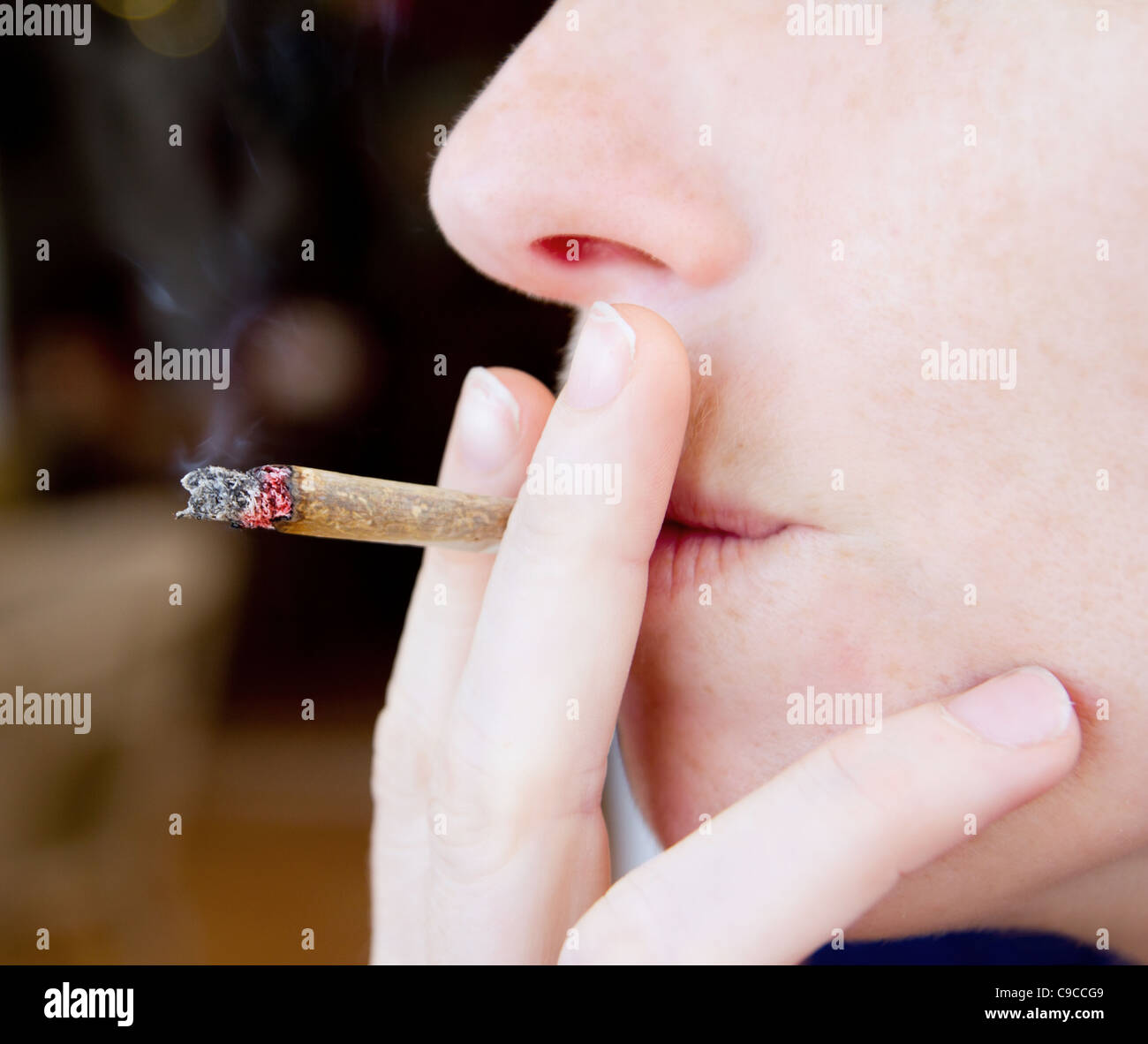 smoking joint closeup with smoke like unhealthy tobacco - Stock Image