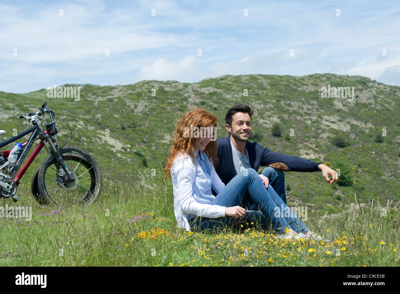 Couple sitting on meadow by mountain bikes Stock Photo