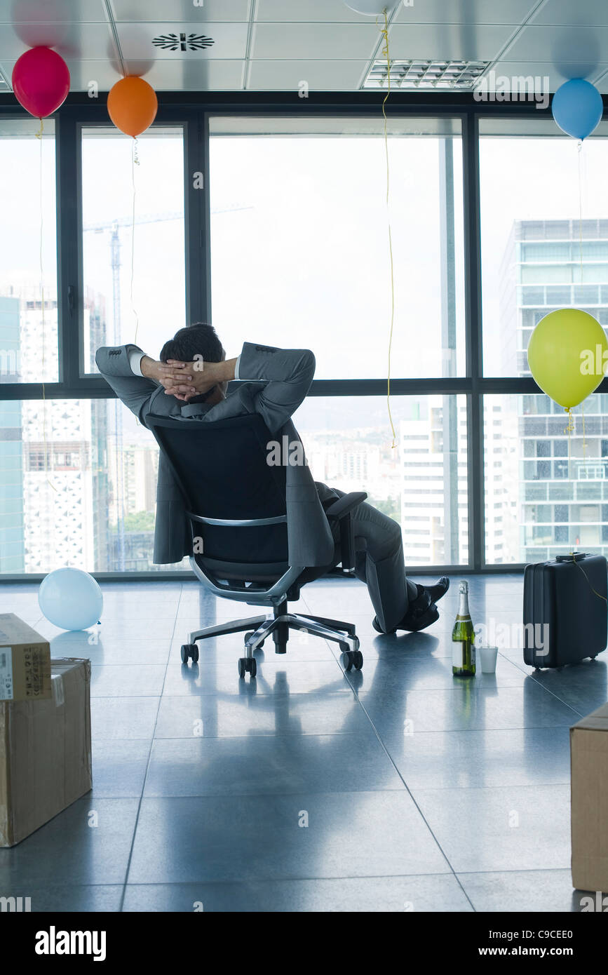 Businessman sitting in new office with balloons and boxes - Stock Image
