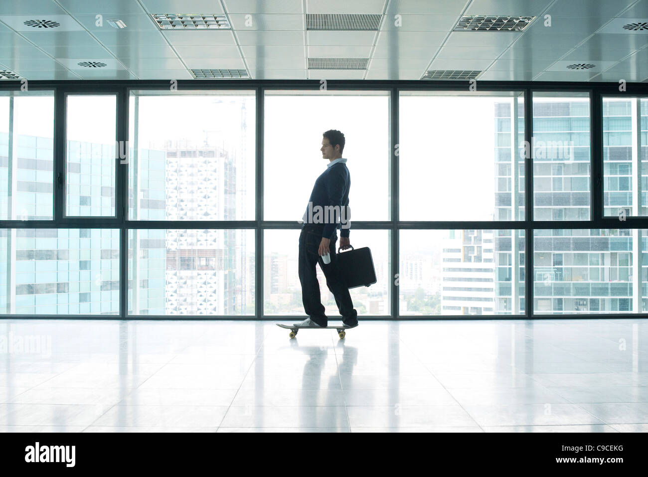 Businessman standing on skateboard with briefcase - Stock Image