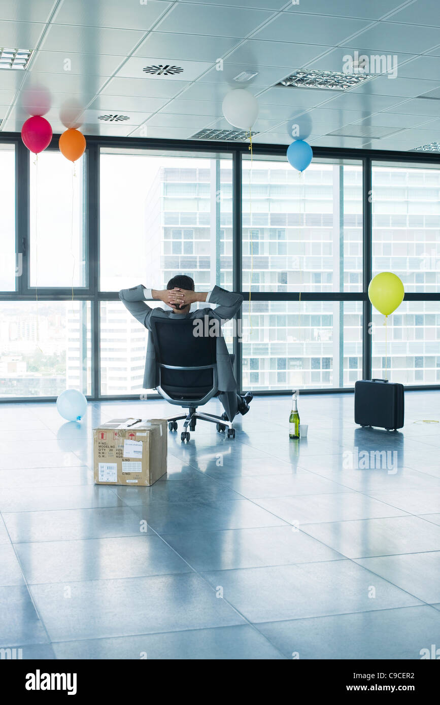 Businessman sitting in new office with balloons and box - Stock Image