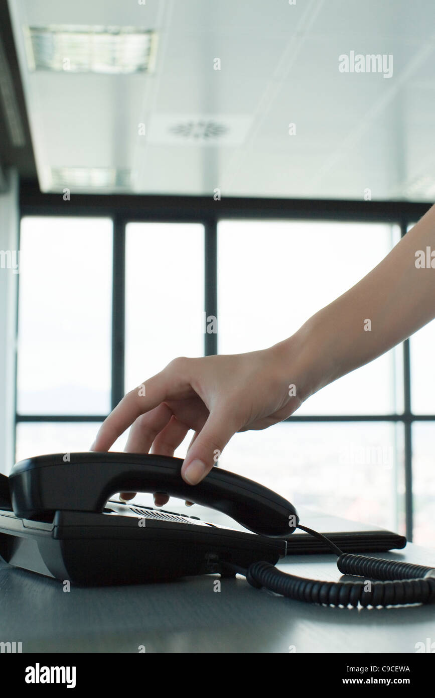 Hand picking up telephone receiver, backlit, cropped - Stock Image