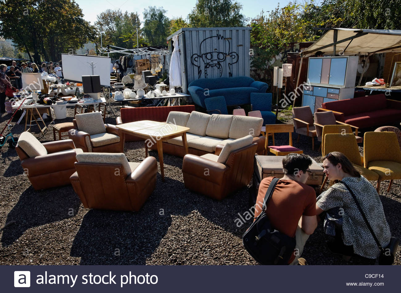 young couple inspecting old furniture at the Mauerpark flea market in Berlin - Stock Image