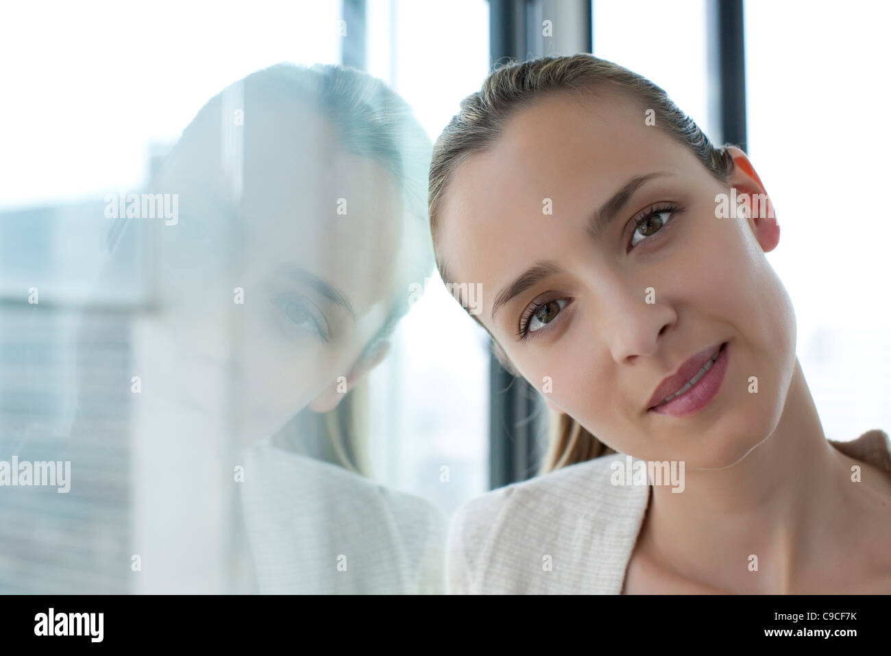 Woman leaning against window, head tilted - Stock Image