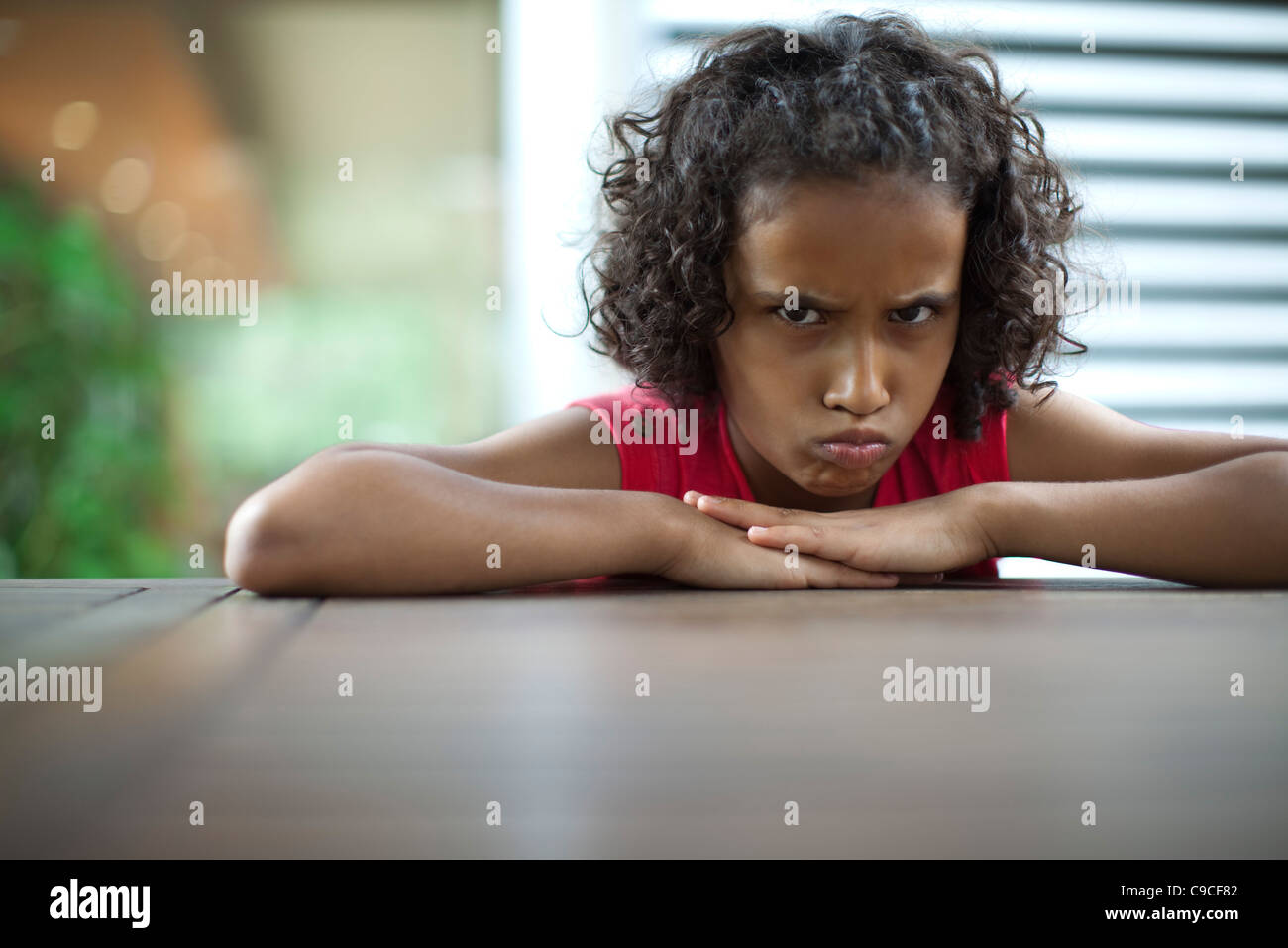 Sulky girl scowling at camera - Stock Image