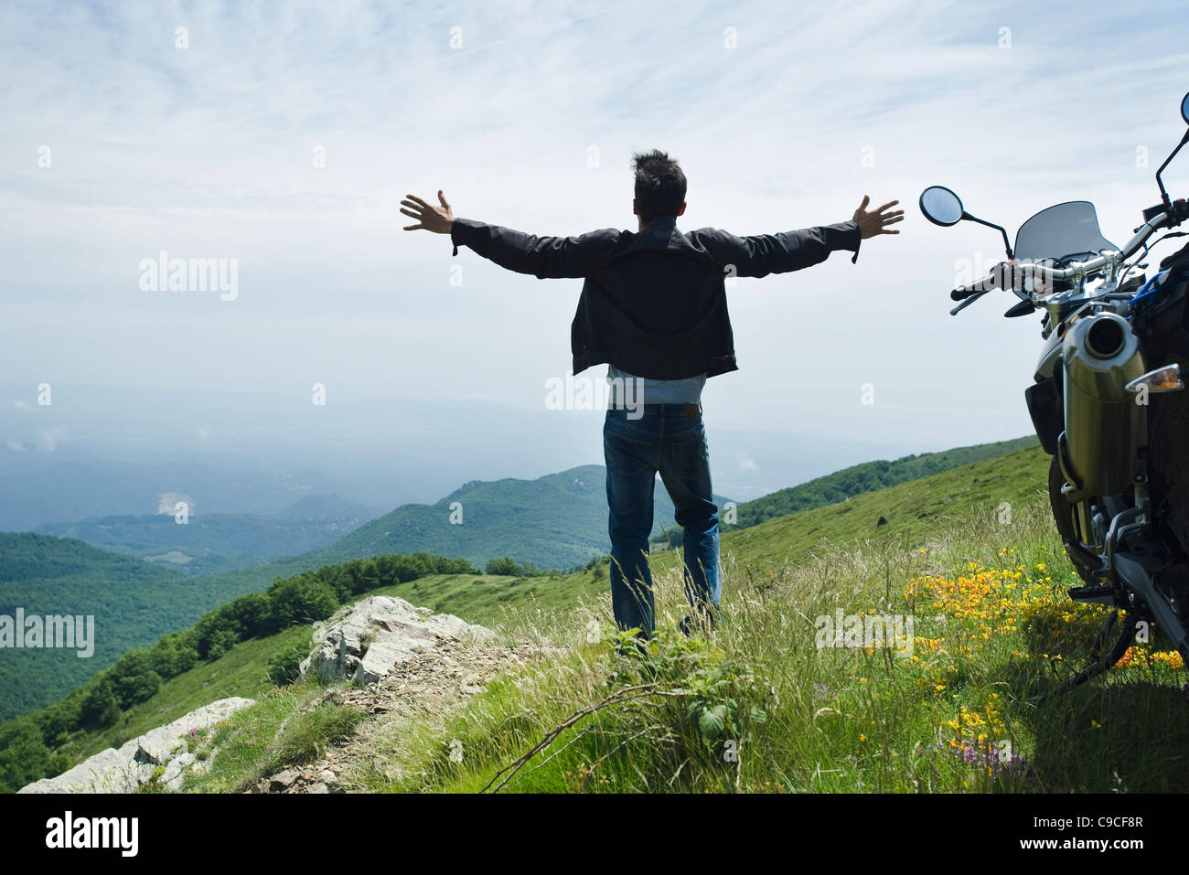 Man standing by motorcycle on top of mountain, arms outstretched - Stock Image