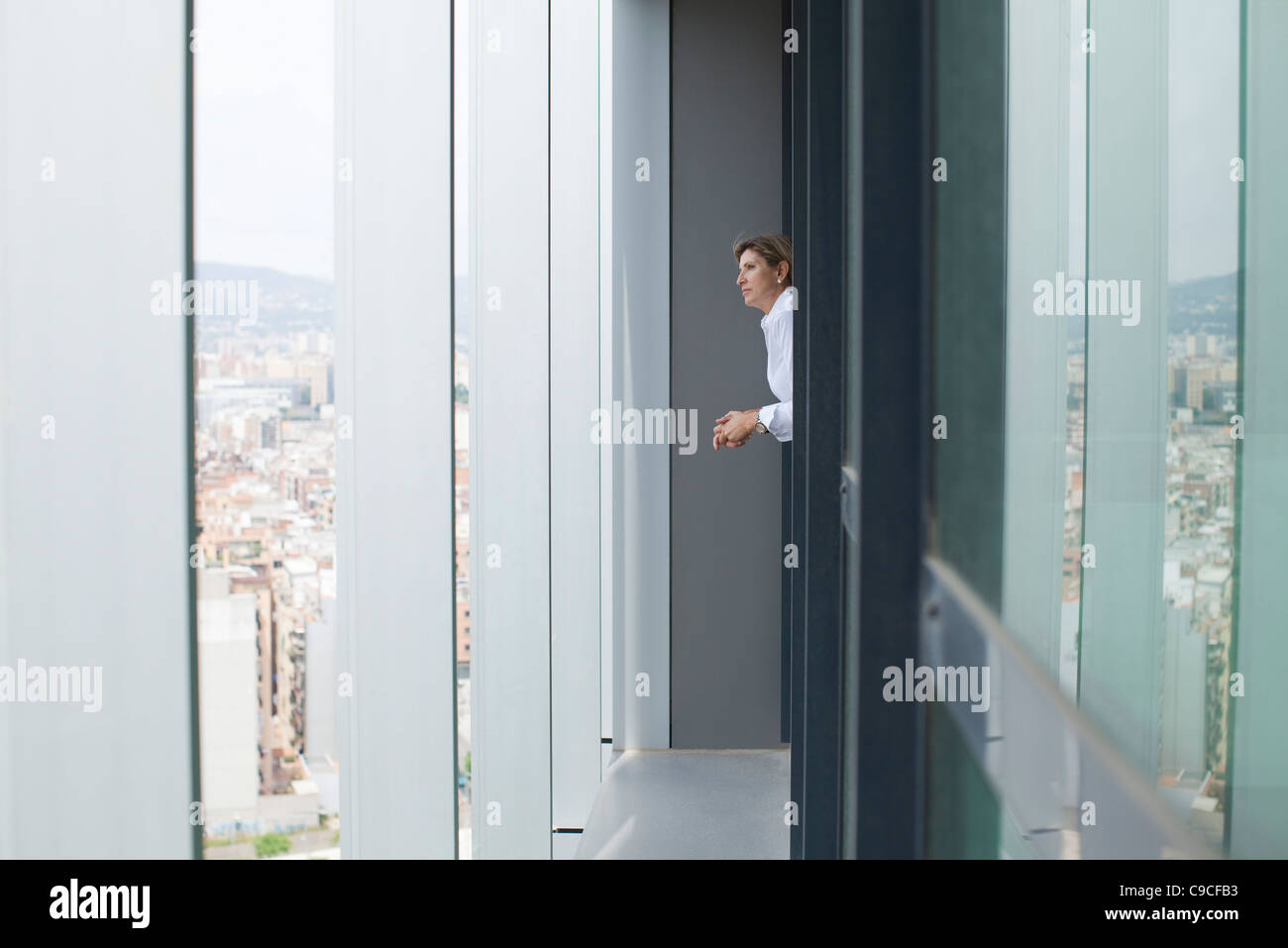 Woman looking out of office window at view of city - Stock Image