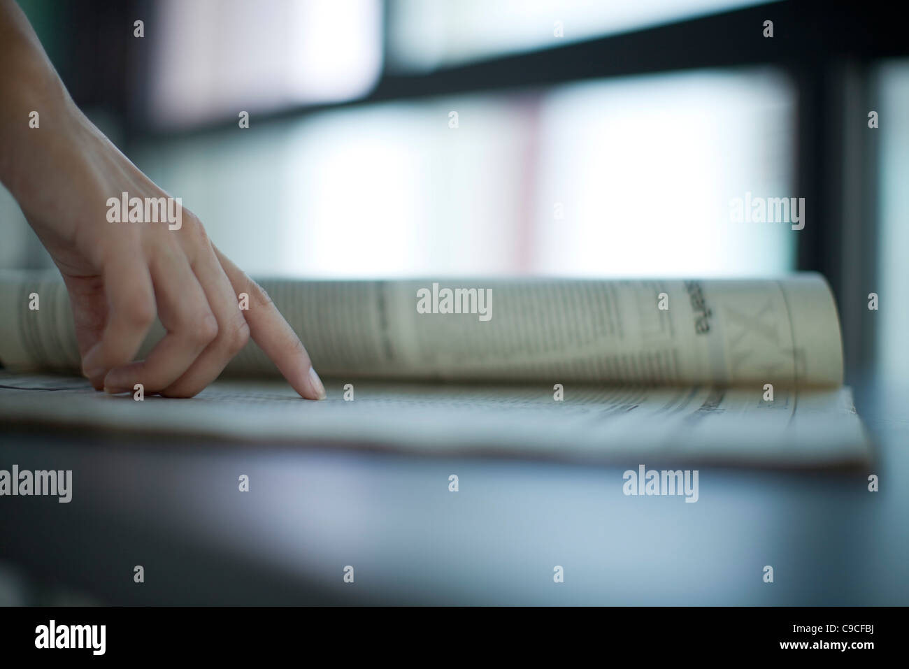Hand pointing at newspaper, backlit, cropped - Stock Image