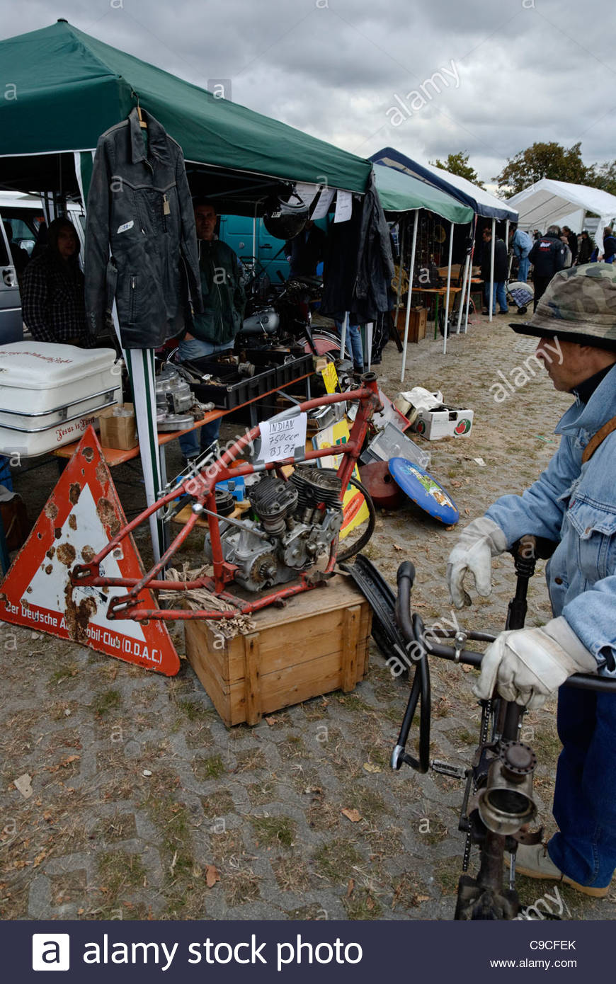 man looking at vintage indian motorcycle restoration project for