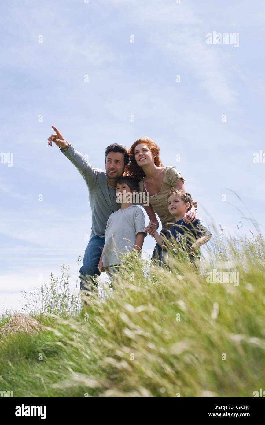 Parents and two boys standing on meadow, father pointing into distance - Stock Image