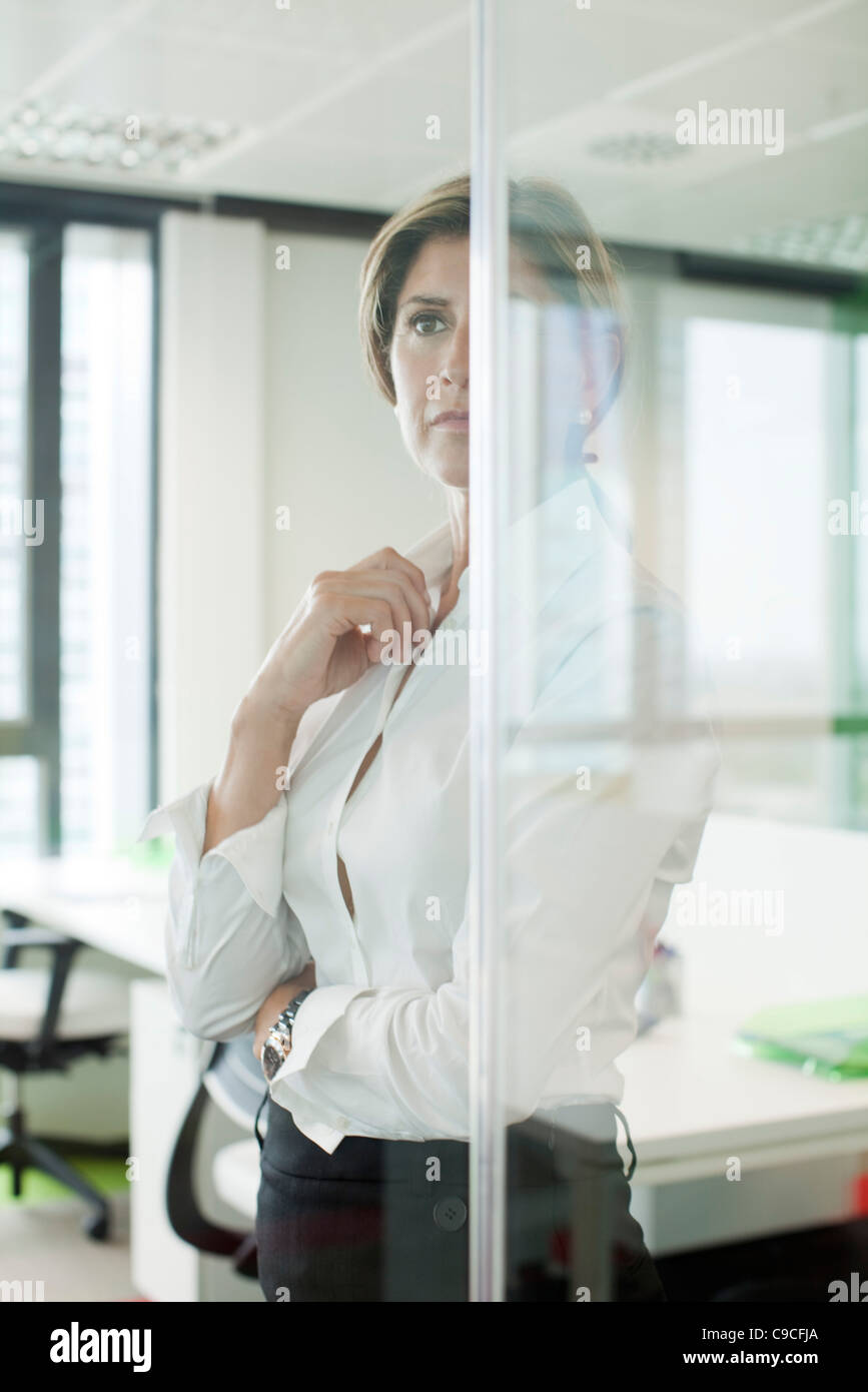 Businesswoman standing behind glass partition in office - Stock Image