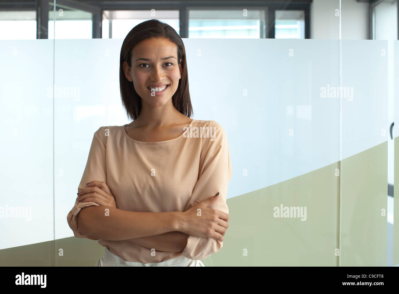 Smiling woman in office, portrait - Stock Image