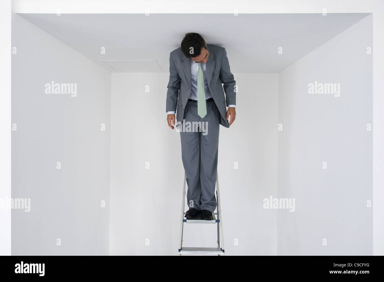Executive standing on stepladder - Stock Image