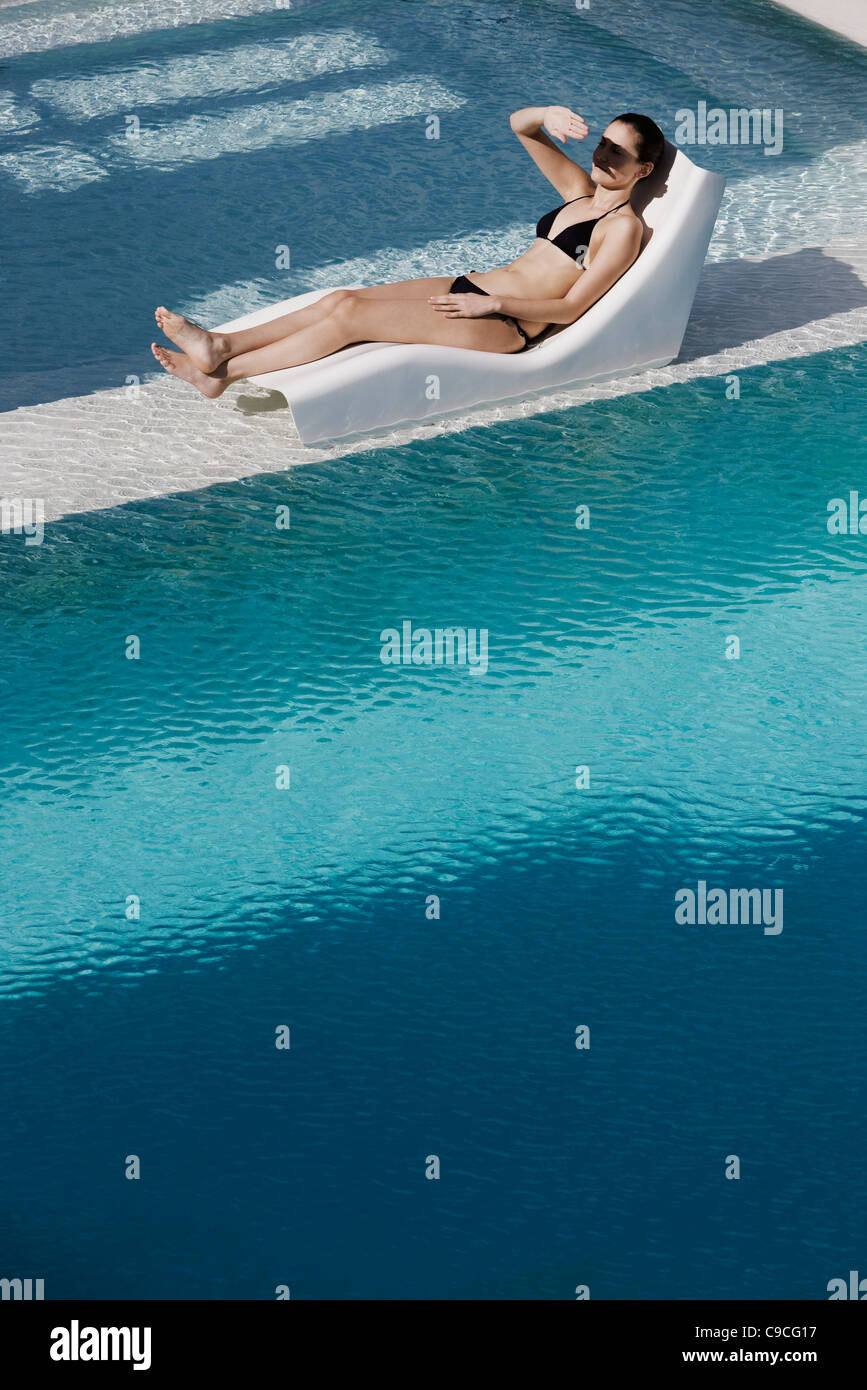 Young woman reclining on poolside deckchair, shading eyes with hand - Stock Image