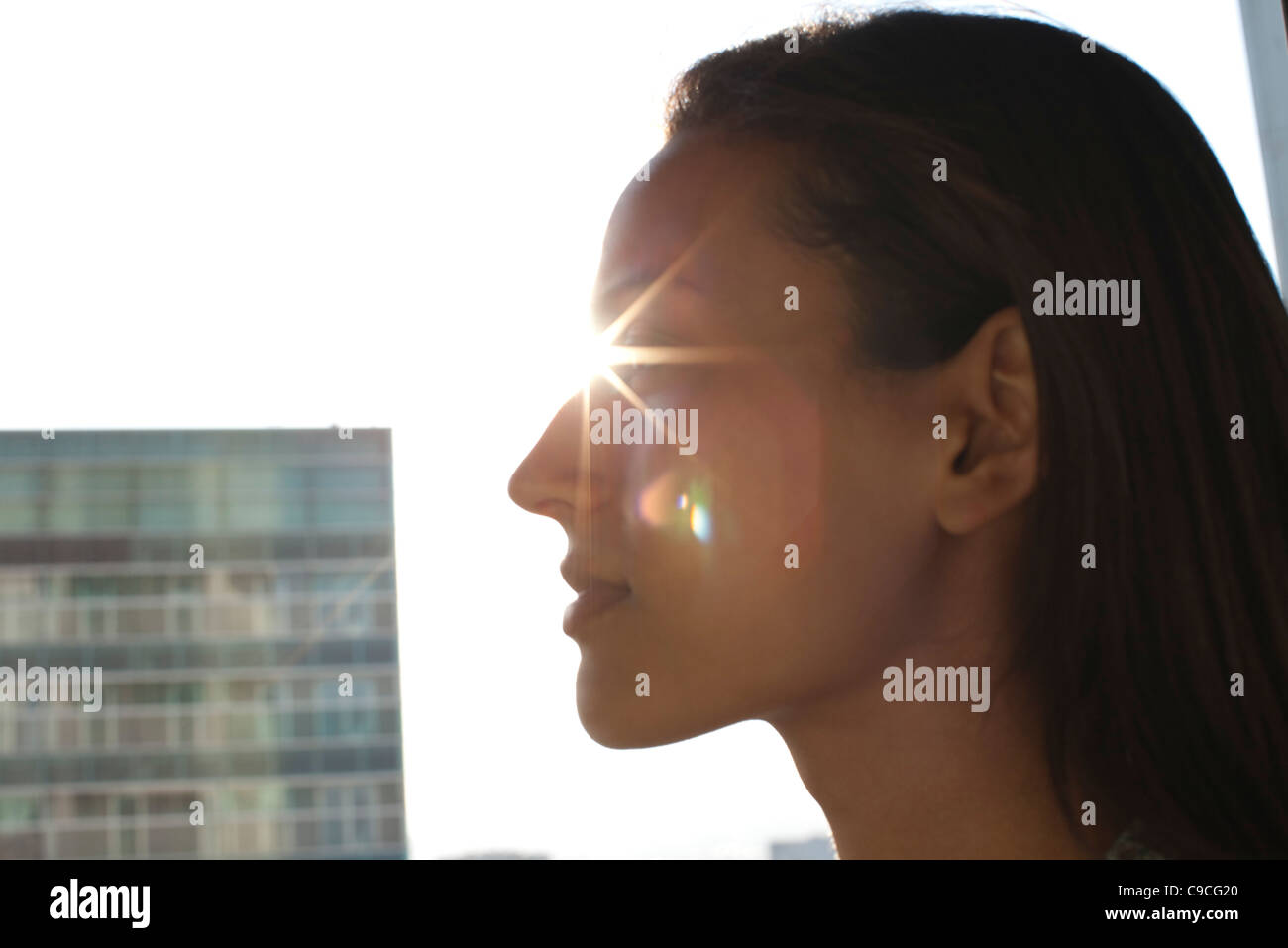 Silhouette of woman's face, sun shinning in background - Stock Image