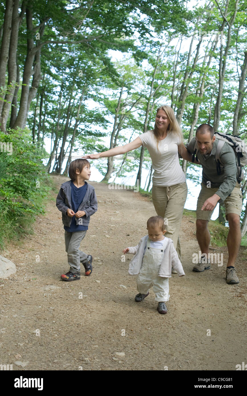 Parents playing with children in woods - Stock Image