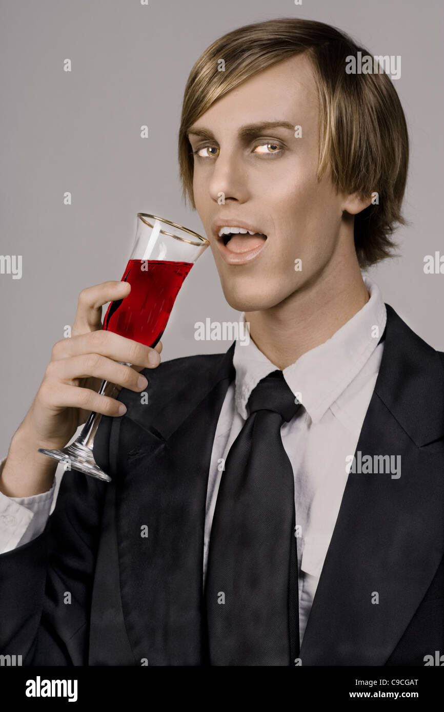 handsome young vampire drinking form Champaign glass - Stock Image