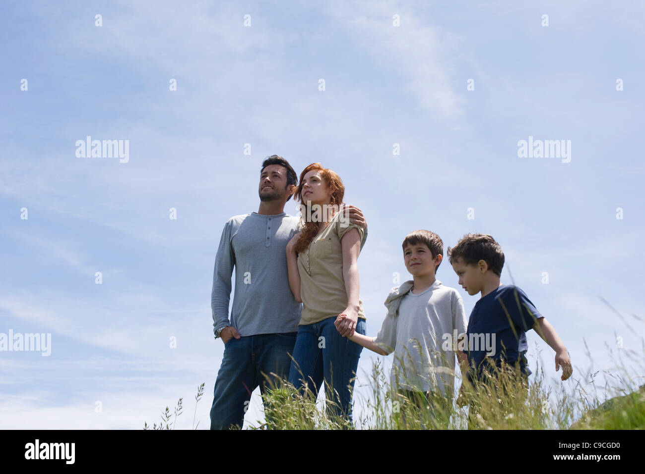 Parents and two boys standing on meadow holding hands, low angle view - Stock Image