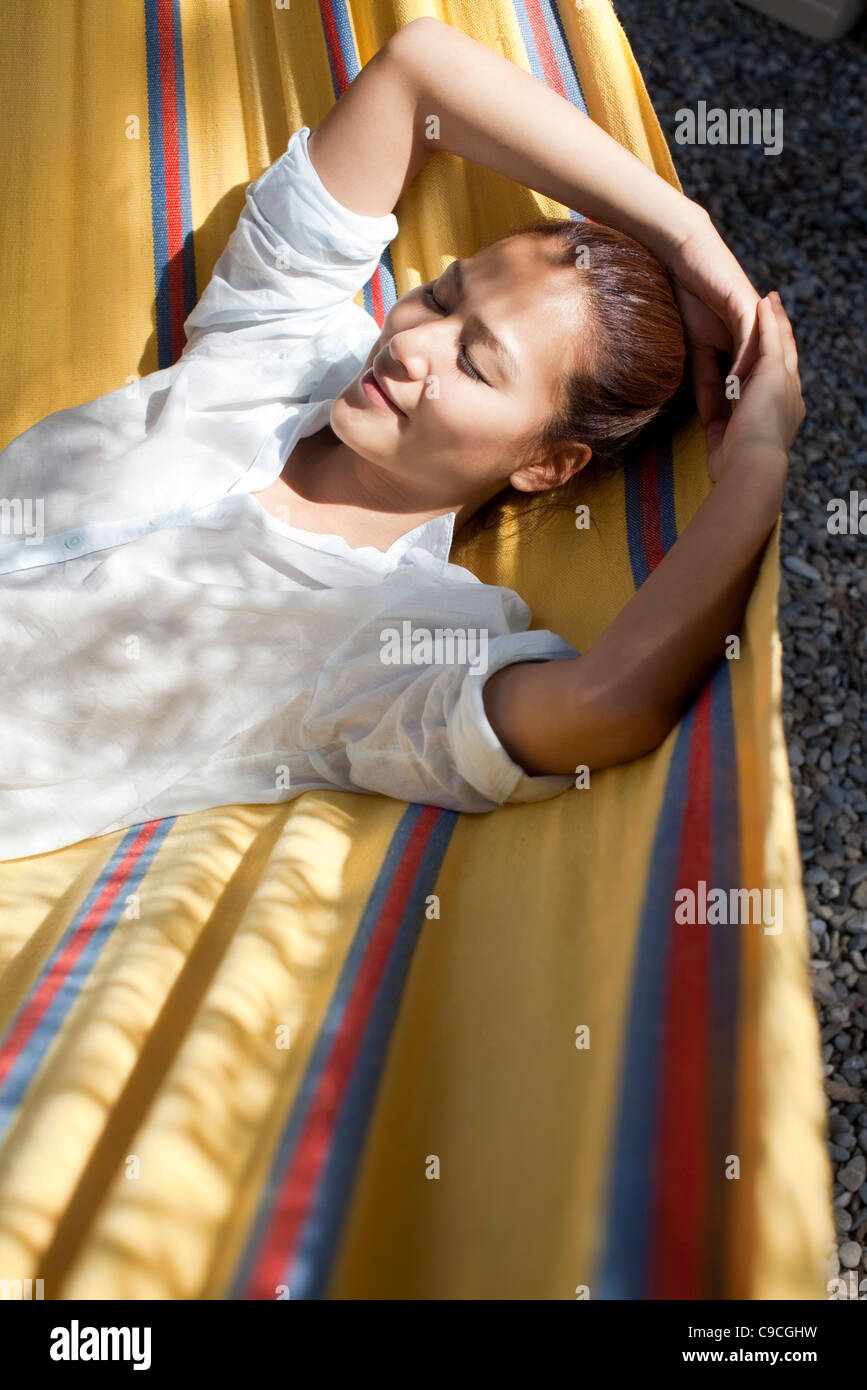 Woman napping in hammock - Stock Image