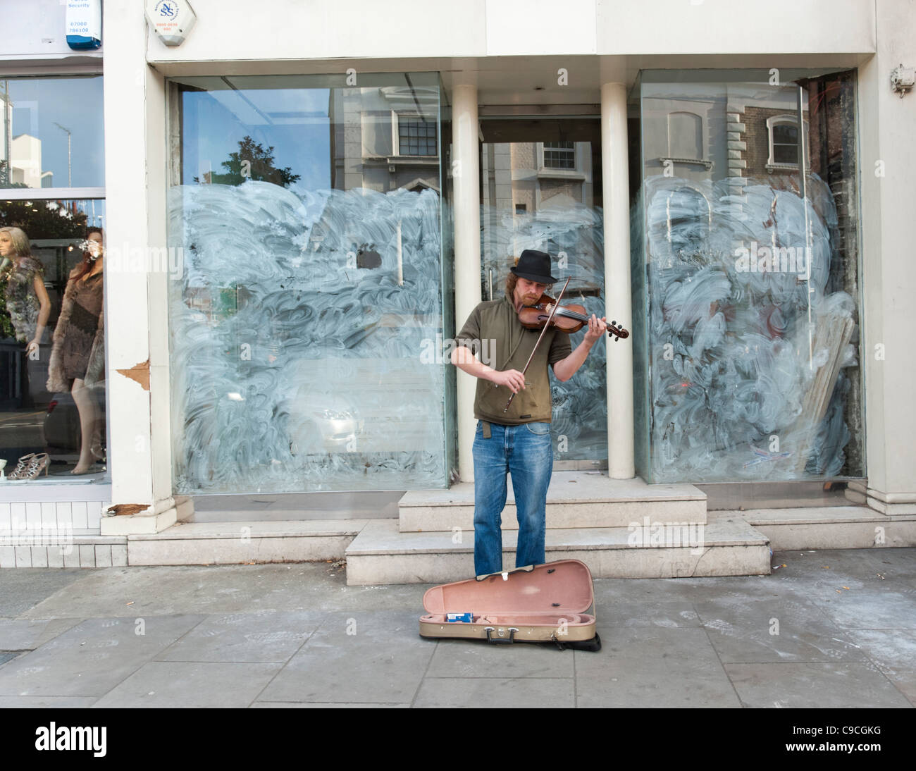 Busker playing violin outside closed down shop on the King's Road, London, UK - Stock Image