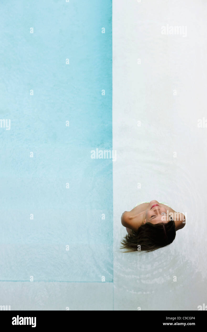 Woman in wading pool with look of contentment - Stock Image
