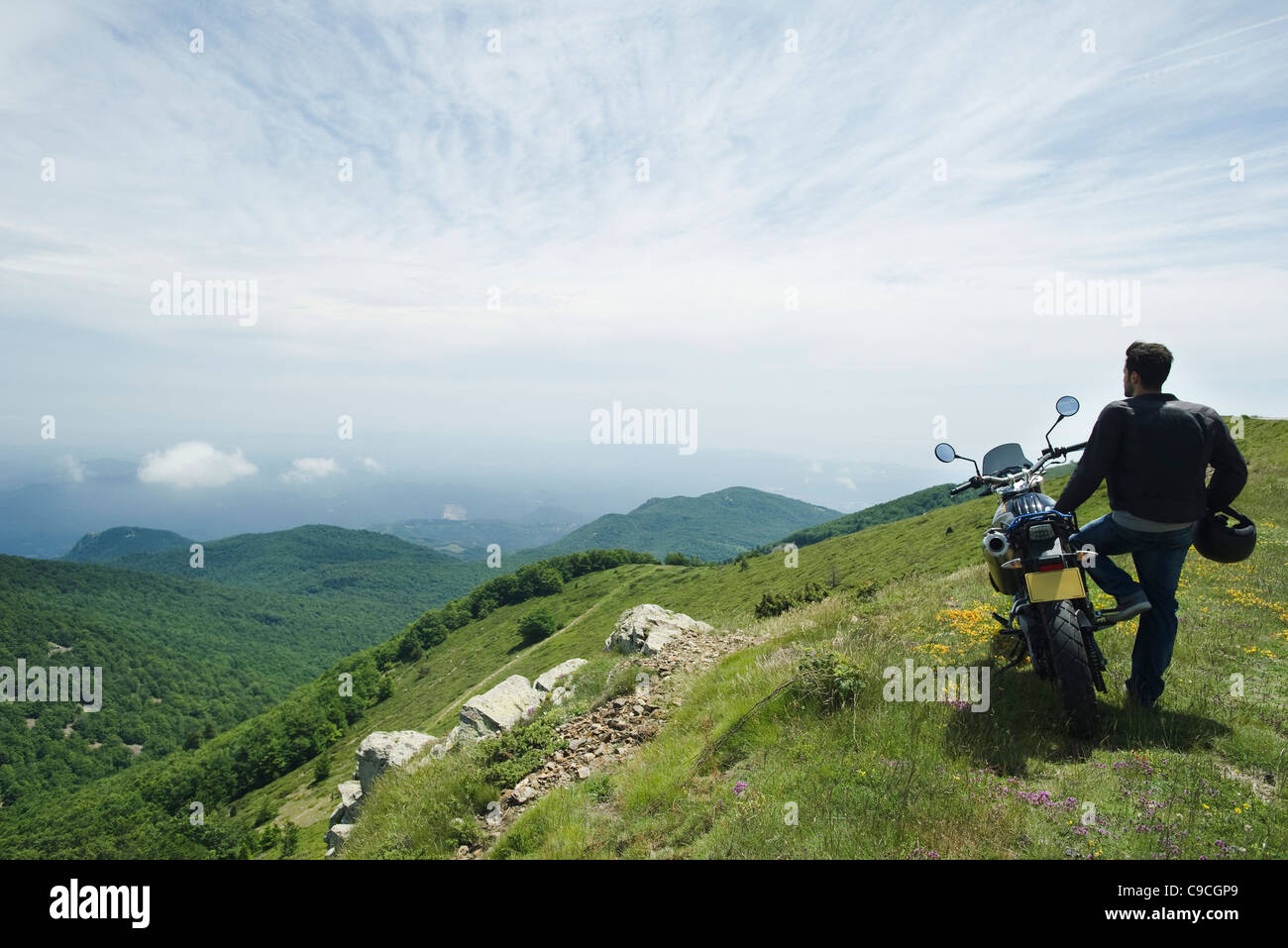 Man standing by motorcycle on top of mountain, rear view - Stock Image