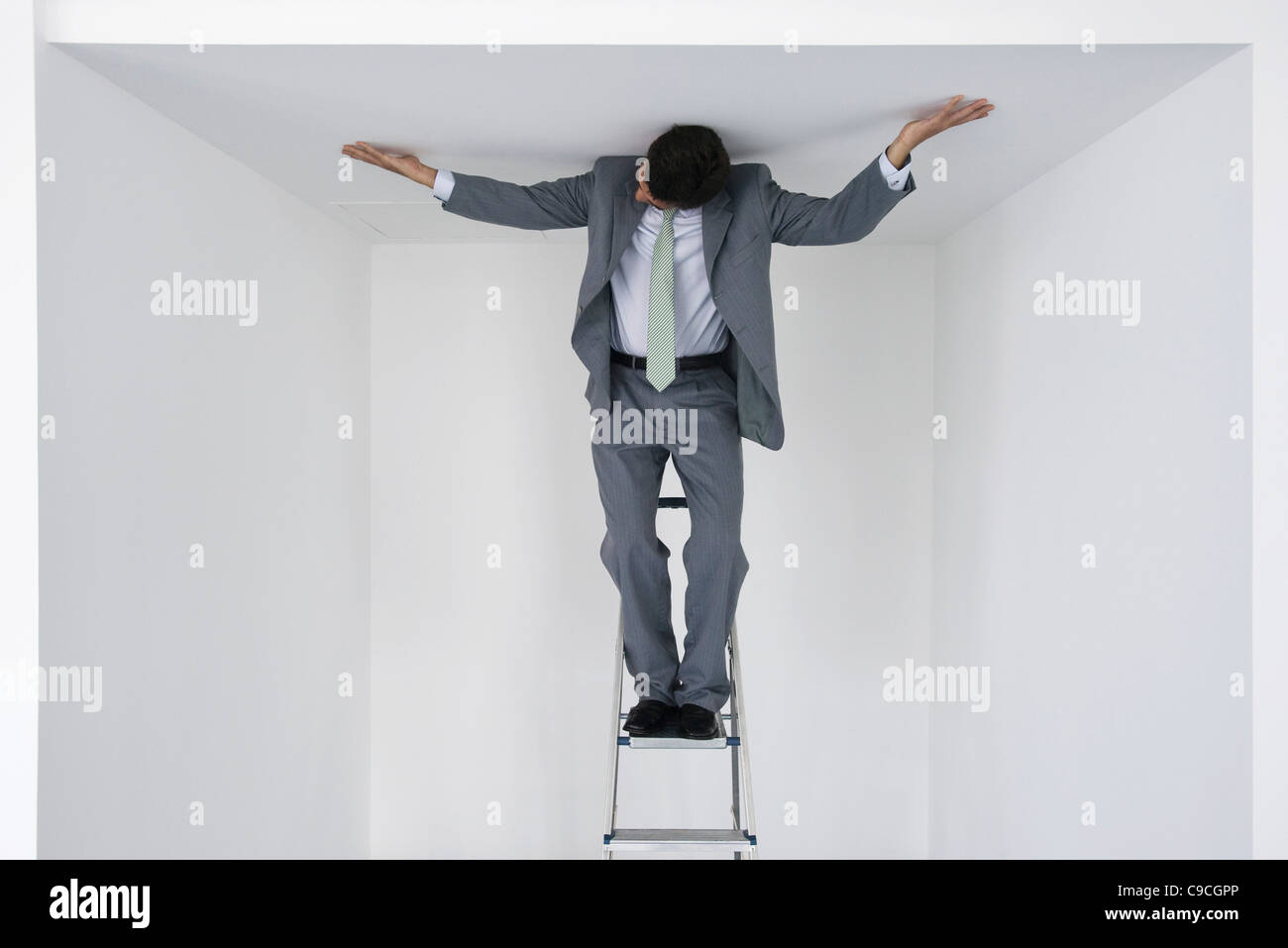 Executive standing on stepladder, arms outstretched on ceiling Stock Photo