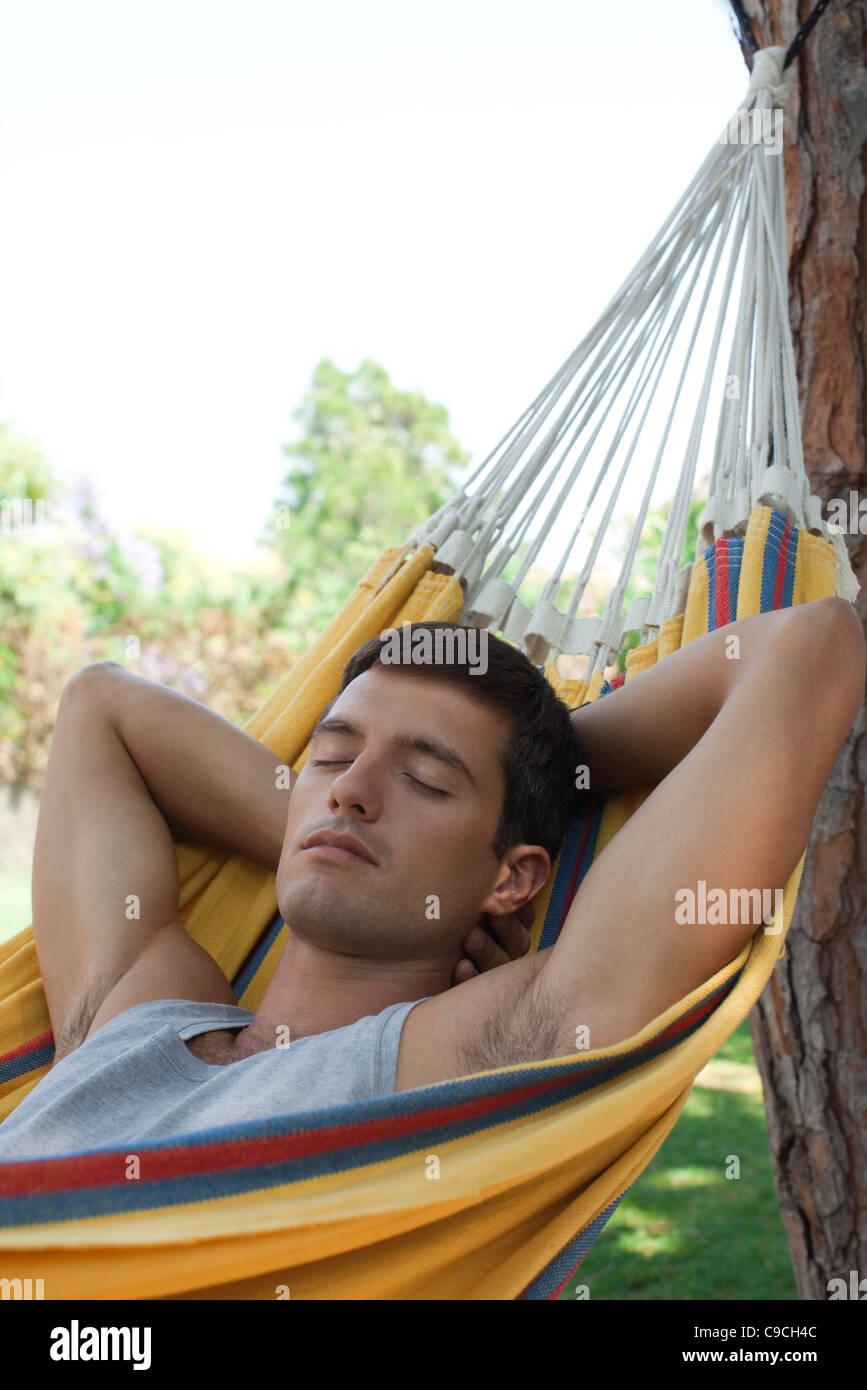 Man napping in hammock - Stock Image