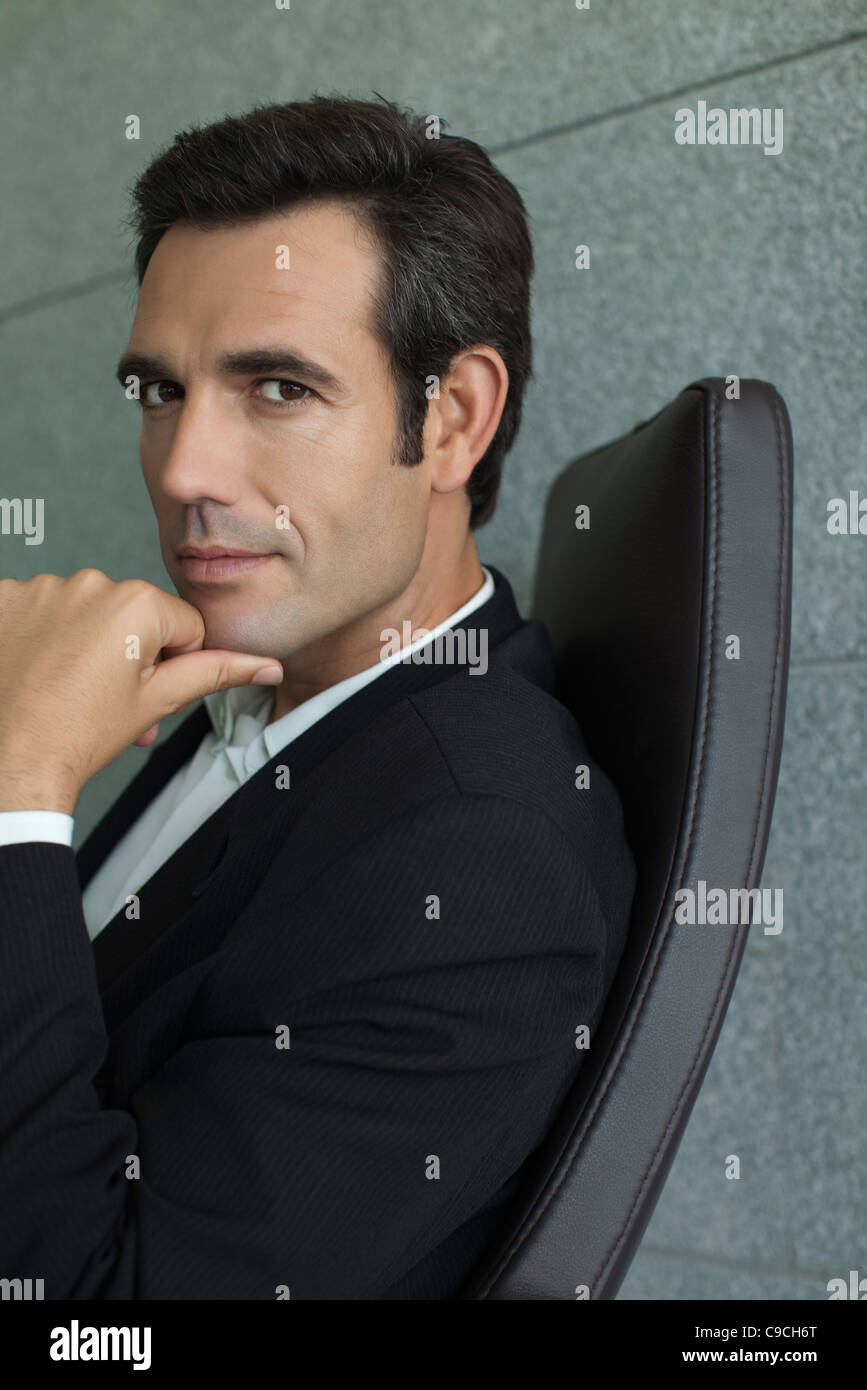 Executive with hand under chin, portrait - Stock Image