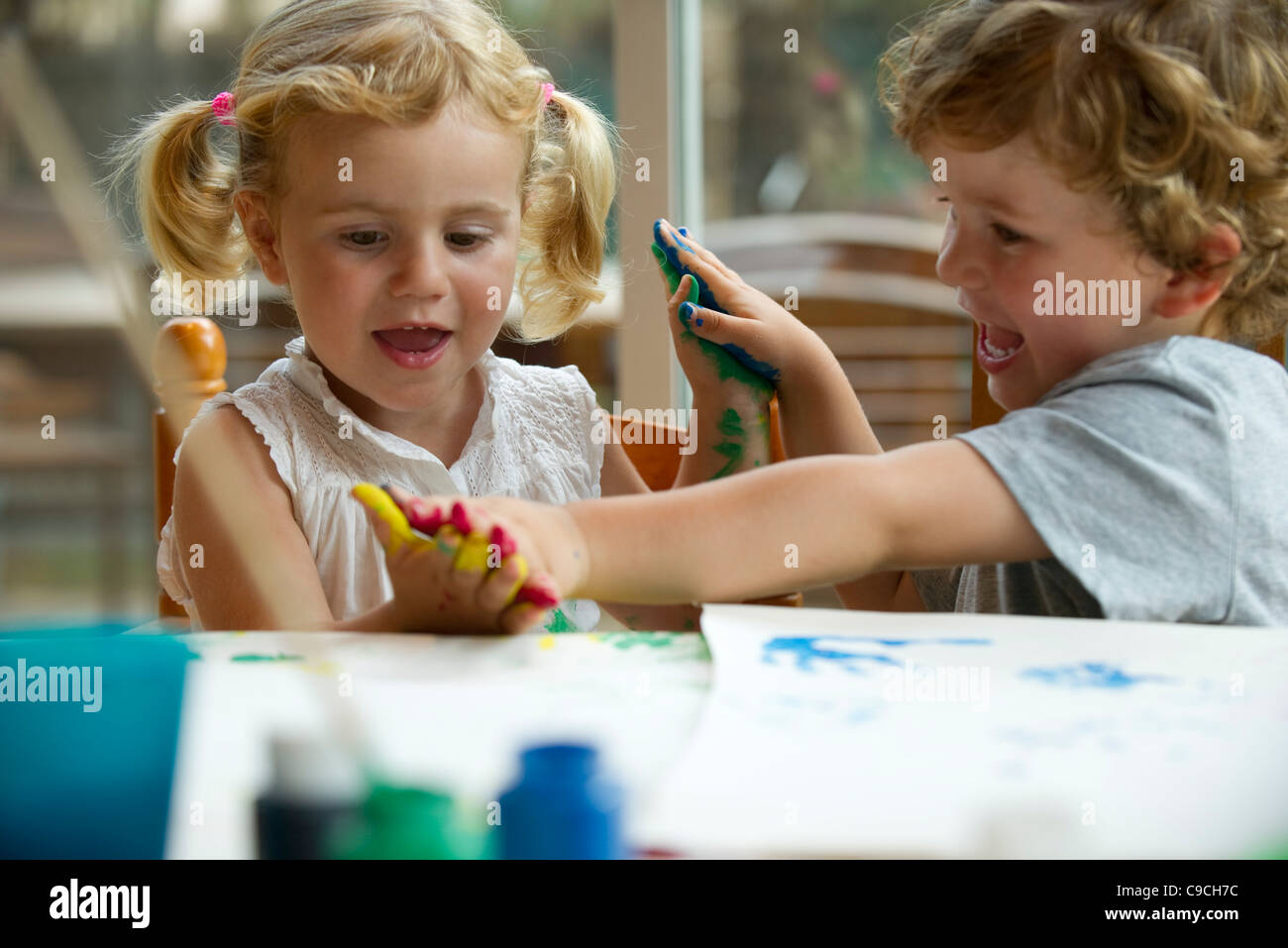 Children playing with paint together - Stock Image