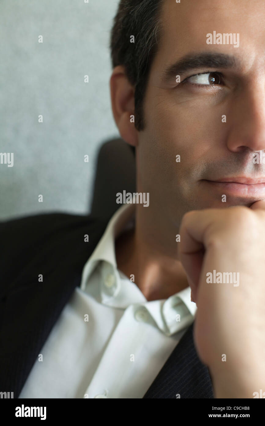 Executive with hand under chin, close-up, cropped - Stock Image