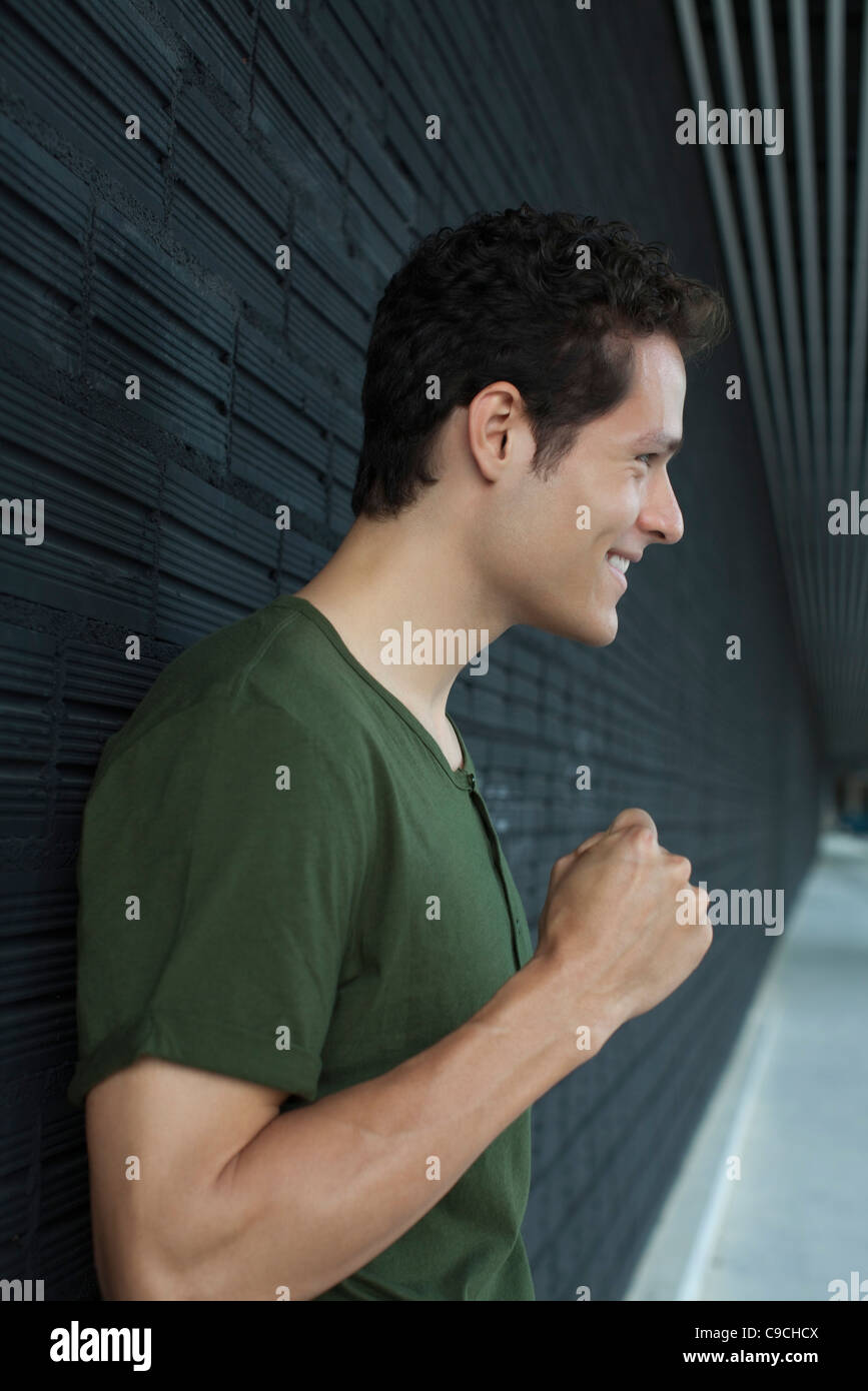 Smiling man holding up fist - Stock Image