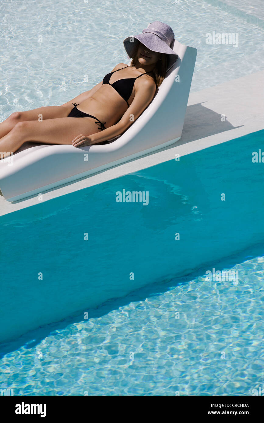 Young woman wearing sun hat reclining on poolside deckchair - Stock Image