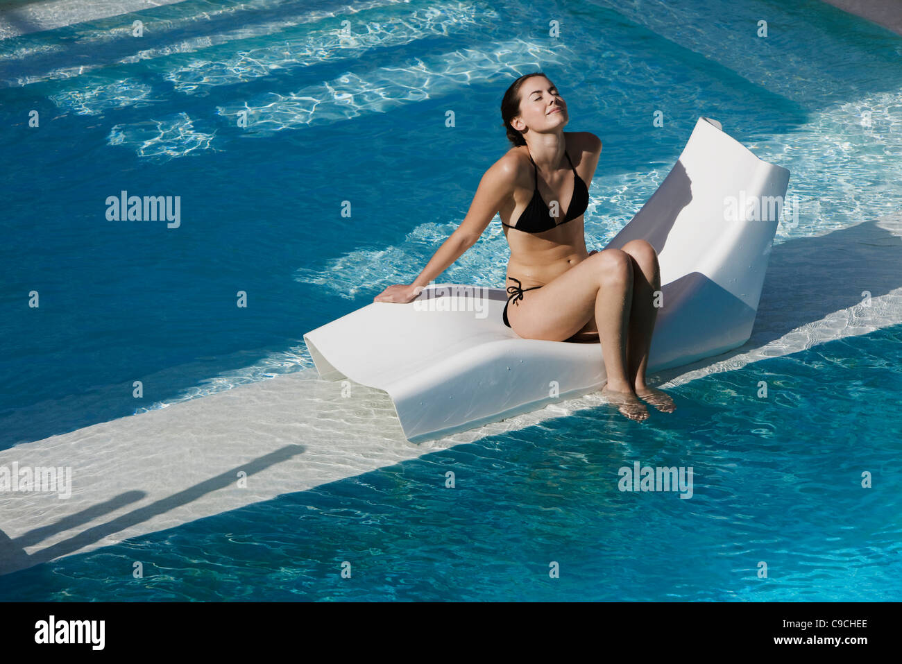 Young woman sitting on poolside deckchair dangling feet into water - Stock Image